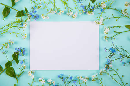 Clear sheet of white paper surrounded with blue and white little flowers on light mint background. Spring card with empty space.