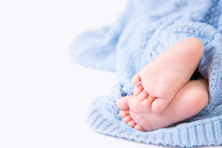 Closeup barefooted tender baby feet wrapped in blue knitted natural plaid on white background. Concept of child comfort. Stock Photo