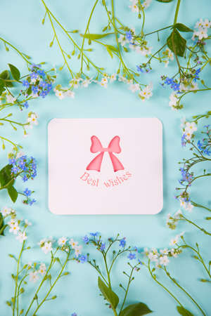 Greeting card with inscription Best wishes surrounded with blue and white little flowers on light mint background. Spring card with flower frame.