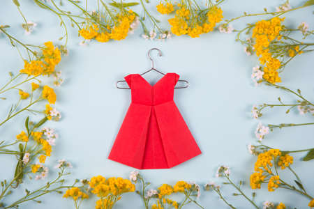 Red paper origami dress on hanger surrounded with yellow and white little flowers on light mint background. Tender Mothers Day card. Concept of spring fashion.