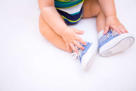 Legs of baby boy dressed in childrens blue sneakers on lacing on white background. Concept of first shoes. Stock Photo