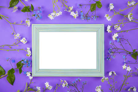Empty photo frame surrounded with blue and white little flowers on violet background. Spring card with clear space. Stock Photo