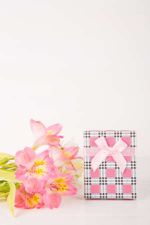 Pink gift box with tender bouquet of beautiful alstroemeria flowers on white wooden background. Spring card for womens or mothers day with empty space.