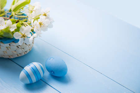 Two painted blue Easter eggs near basket with white spring flowering branch on light blue background.