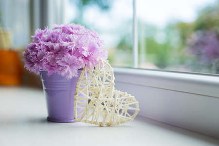 Little purple bucket with tender bouquet of beautiful pink carnation and white wicker rattan heart near window in daylight. Spring mother's day gift.