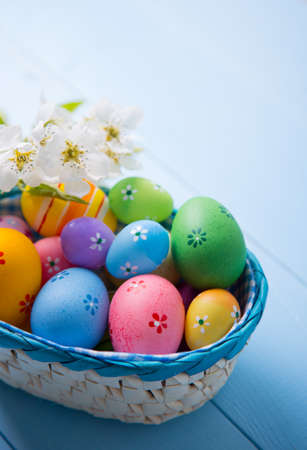 Variety of decorated colorful Easter eggs in basket with white spring flowers on light blue background.