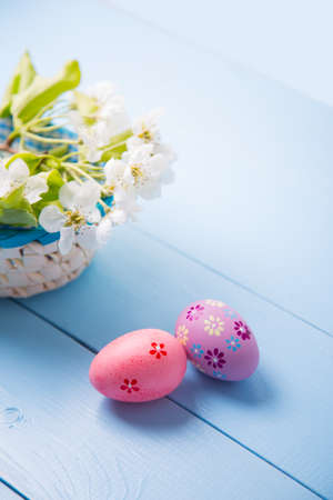 Two painted pink Easter eggs near basket with white spring flowering branch on light blue background.