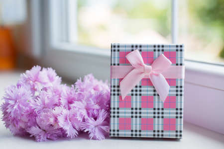 Bouquet of tender pink carnation flowers with gift box near window in daylight. Spring Mother's day gift.