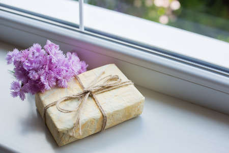 Vintage gift box with tender bouquet of pink carnation flowers near window in daylight. Spring composition. Stock Photo