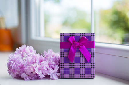 Bouquet of tender pink carnation flowers with purple gift box near window in daylight. Spring Mother's day gift.