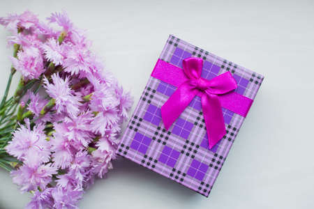 Bouquet of tender pink carnation flowers with purple gift box on light background in daylight. Spring Mother's day gift.
