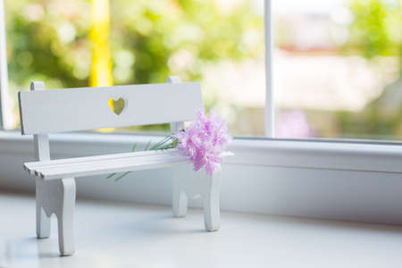 Bouquet of beautiful tender pink carnation on white bench with hole in form of heart near window in daylight. Spring composition.
