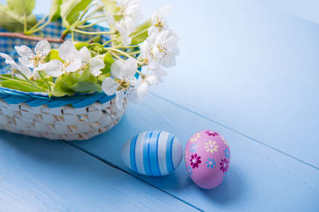 Two painted Easter eggs near basket with white spring flowering branch on light blue background. Stock Photo