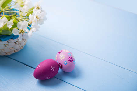 Two painted crimson Easter eggs near basket with white spring flowering branch on light blue background.