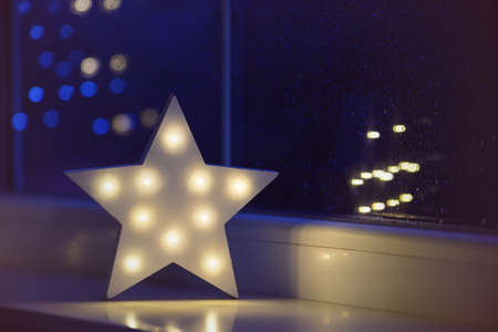 White LED star near window on garland bokeh background indoor in evening time. Festive spring illumination, holiday atmosphere. Stock Photo