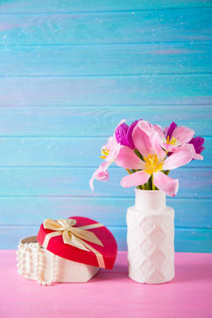 Open gift box with pearl necklace and tender bouquet of beautiful pink tulips in white vase on blue and pink wooden background. Romantic spring gift.