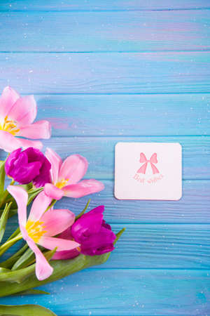 Greeting card with inscription Best wishes and tender bouquet of beautiful pink tulips on creative blue wooden background. Concept of spring gift. Stock Photo