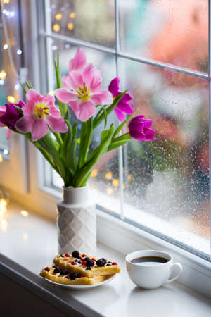 Cup of coffee, wafers with berries and white vase with tender bouquet of beautiful pink tulips near window with raindrops in the daylight. Spring blooming flowers with garland lights on background. Concept of spring dessert. Stock Photo
