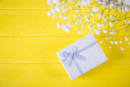 Gift box and fresh bouquet of white gypsophila on yellow wooden background. Concept of Mothers day gift.