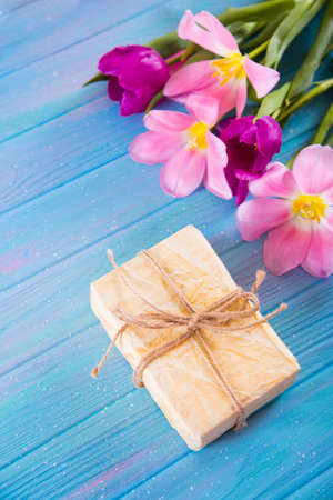 Crafted gift box and tender bouquet of beautiful pink tulips on creative blue wooden background. Concept of spring gift.