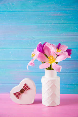 Gift box in shape of heart and tender bouquet of beautiful pink tulips in white vase on blue and pink wooden background.