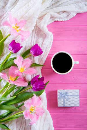 Cup of coffee, white gift box and tender bouquet of beautiful tulips on pink wooden background. Spring gift.
