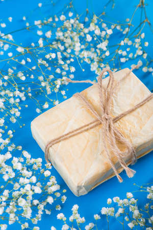Crafted gift box surrounded by white gypsophila flowers on blue background. Concept of Mothers day gift.