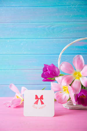 Greeting card with inscription Best wishes and tender bouquet of beautiful pink tulips in wicker basket on blue wooden background. Spring gift.