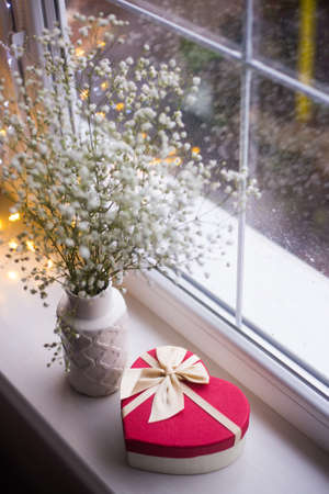 Red gift box in shape of heart and bouquet of beautiful white gypsophila near window with raindrops in the daylight, garland lights on background. Stock Photo