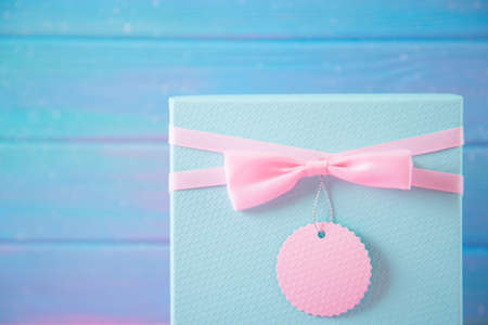 Closeup cute mint blue gift box with pink bow and label for signature and greetings on blue wooden background.