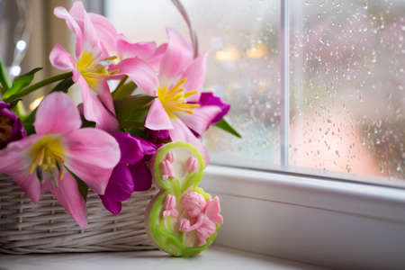 Decorative figure eight and tender bouquet of beautiful pink tulips in white basket near window with raindrops in the daylight. Spring blooming flowers with garland lights on background. Concept of Womens day gift. Stock Photo