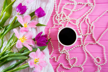 Cup of coffee, white pearl necklace and tender bouquet of beautiful tulips on pink wooden background. Spring morning.