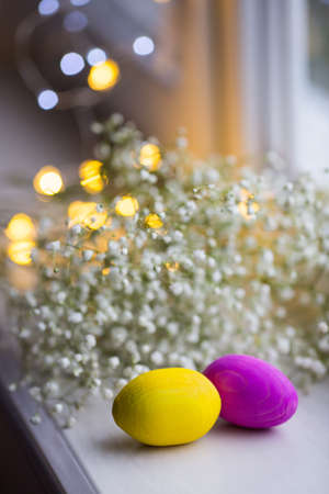 Two colored wooden Easter eggs with white gypsophila flowers and garland lights on background in daylight.