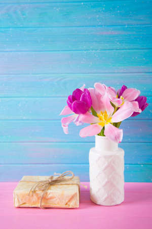 Crafted gift box and tender bouquet of beautiful pink tulips in vase on blue and pink wooden background. Stock Photo