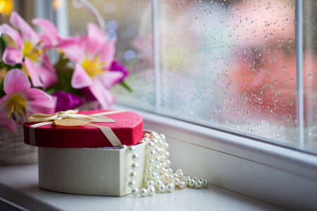 Gift box with white pearl necklace near near window with raindrops in the daylight. Pink tulips on background. Concept of spring Mothers day gift.