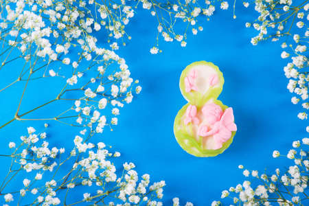 Decorative figure eight surrounded by white gypsophila flowers on blue background. Concept of Womens day gift. Stock Photo