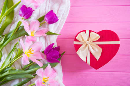 Red gift box in shape of heart and tender bouquet of beautiful tulips on pink wooden background. Concept of romantic surprise.