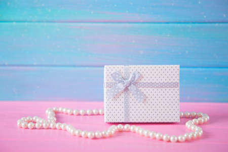 White gift box surrounded by pearl necklace on blue and pink wooden background. Concept of Womens day gift. Stock Photo