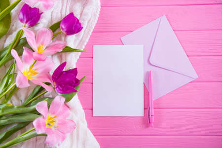 Clear sheet of white paper with pen and envelope and tender bouquet of beautiful tulips on pink wooden background. Spring greeting card with empty space.