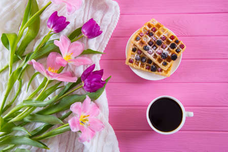 Cup of coffee, wafers with berries and tender bouquet of beautiful tulips on pink wooden background. Concept of spring dessert.