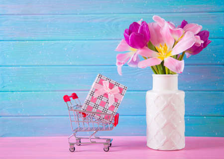 Small supermarket trolley with gift box and tender bouquet of beautiful pink tulips in vase on blue and pink wooden background. Concept of spring purchases.