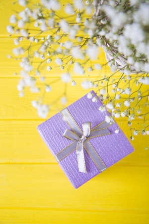 Gift box and fresh bouquet of white gypsophila on yellow wooden background. Concept of Mothers day gift Stock Photo