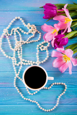 Cup of coffee, white pearl necklace and tender bouquet of beautiful tulips on blue wooden background. Spring morning.