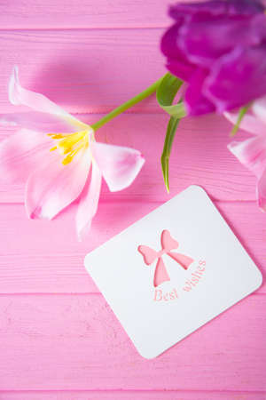 Greeting card with inscription Best wishes and tender bouquet of beautiful pink tulips on pink wooden background. Spring gift.
