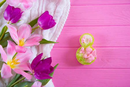 Decorative figure eight and tender bouquet of beautiful tulips on pink wooden background. Concept of Womens day gift.