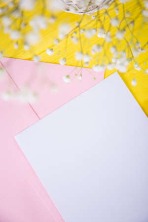 Clear sheet of white paper with envelope and fresh bouquet of white gypsophila on yellow wooden background. Spring card with empty space. Stock Photo