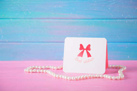 Greeting card with inscription Best wishes surrounded by pearl necklace on blue and pink wooden background. Concept of Womens day gift.