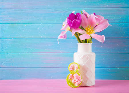 Decorative figure eight and tender bouquet of beautiful tulips in vase on blue wooden background. Concept of Womens day gift.