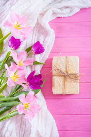 Crafted gift box and tender bouquet of beautiful tulips on pink wooden background. Concept of spring gift. Stock Photo