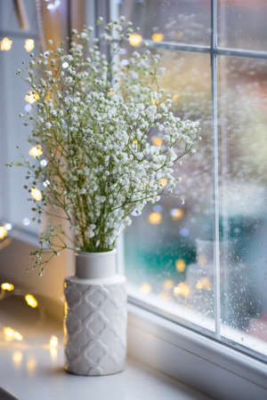 Vase with bouquet of beautiful white gypsophila near window with raindrops in the daylight. Pure flowers with garland lights on background. Stock Photo